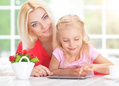 Beautiful  young woman and little girl  sitting at  table and using  tablet