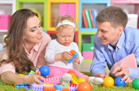 Happy parents playing with little daughter