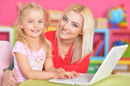 woman and little girl using   laptop Stock Photo