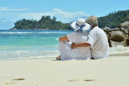Portret van een hoger paar dat op strand rust