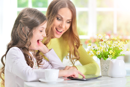 womanly: woman and little girl using  tablet