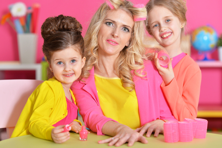 Girls doing manicure and hairstyle for mother
