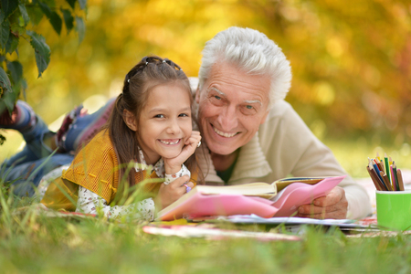 play the old park: Grandfather and  granddaughter reading book Stock Photo
