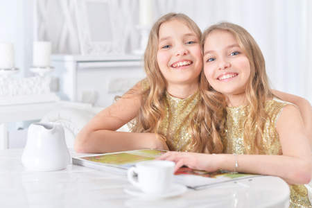 cute twin sisters with modern magazine