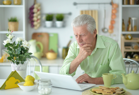 Senior man using modern laptop