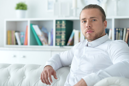 Beau jeune homme sur le canapé Banque d'images - 82154328