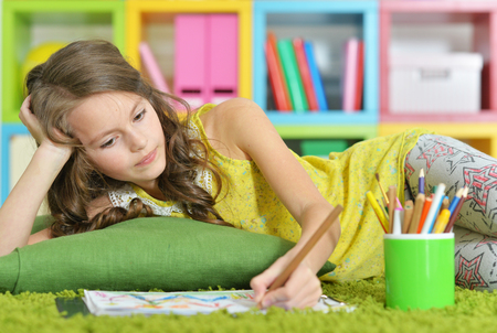 Little girl painting with pencil in her room
