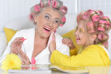 woman and granddaughter doing make up Stock Photo