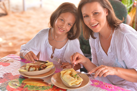 mother and daughter eating in cafe Stock Photo