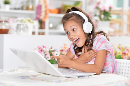 Little girl in headphones sitting at table and using laptop