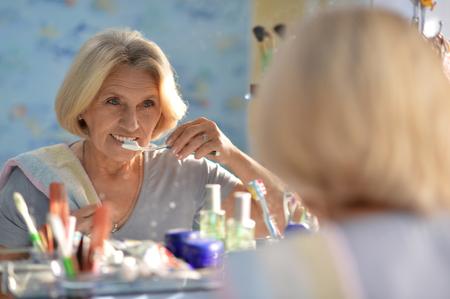 Senior woman brushing her teeth 版權商用圖片 - 84001011