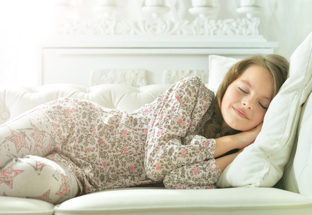 little girl in pajama sleeping on couch