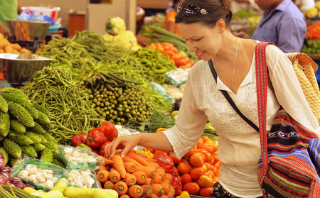 Young woman choosing vegetables Stock Photo
