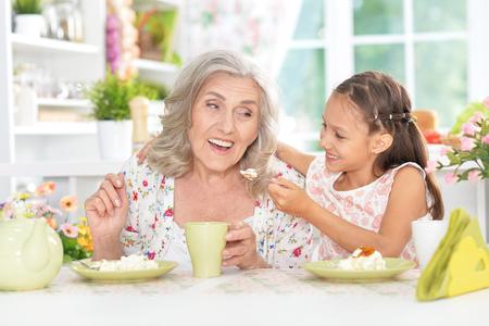niños desayunando: grandmother and granddaughter having breakfast