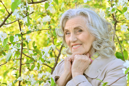 senior woman near blooming tree Banco de Imagens