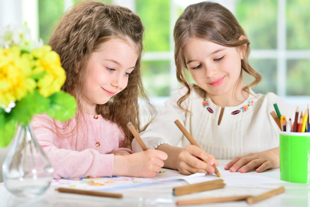 little girls drawing with pencils