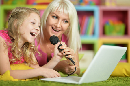 mother and daughter singing karaoke Stock Photo