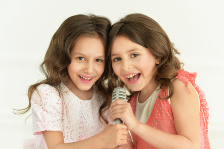 close up view of cute little girls singing with microphone