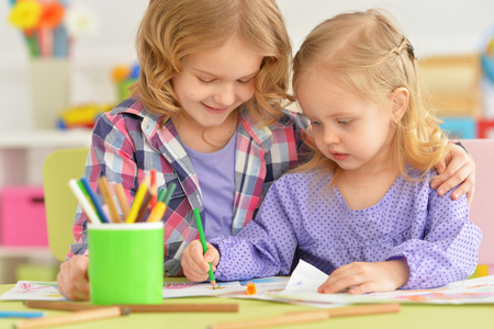 Portrait of a cute little girls drawing together