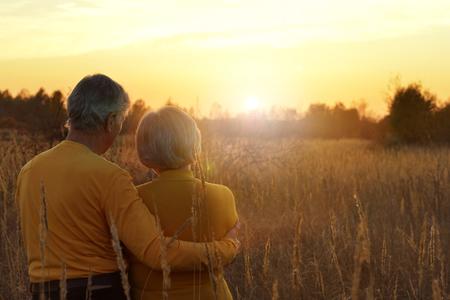 Achtermening van hoger paar op gebied van tarwe tijdens zonsondergang