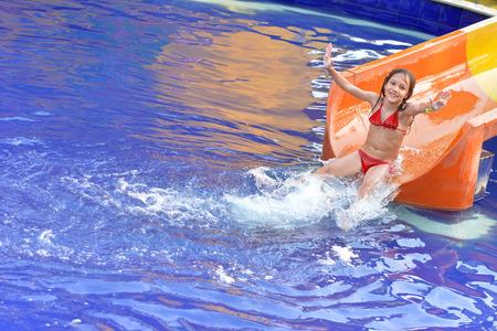 Happy girl on water slide in summer Stock Photo