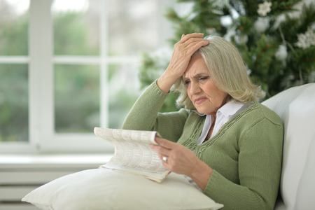 upset senior woman with newspaper
