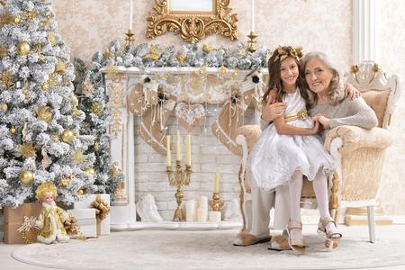 woman and girl decorating Christmas tree together