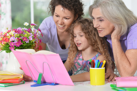 three generations of women from one family doing homework Stock Photo