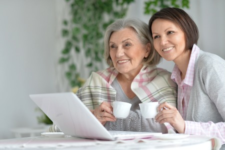 senior mother and adult daughter working with laptop