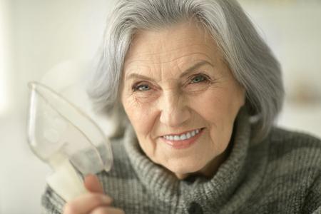 Senior woman making inhalation