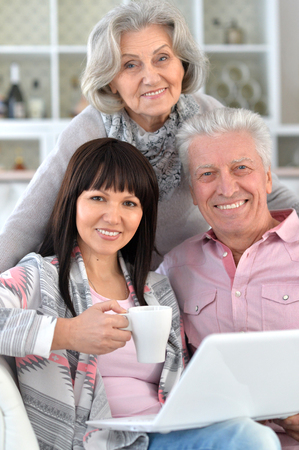 Senior couple portrait with laptop with caring daughter Stock Photo