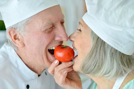 Senior chefs couple with tomato  at kitchen Stock Photo