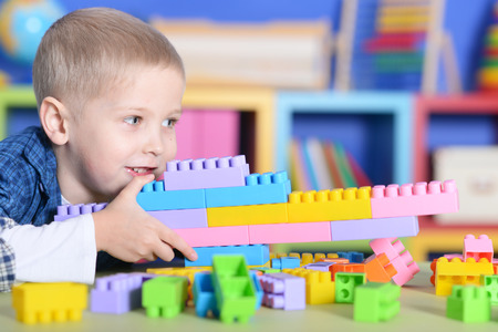 boy playing with colorful plastic blocks