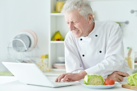 elderly male chef cooking salad Stock Photo