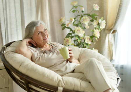 Senior woman resting at home with tea cup Stock Photo