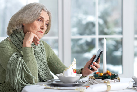 woman sitting at table  with phone