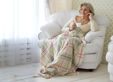 Ältere Frau , die zu Hause mit Teetasse stillsteht Standard-Bild