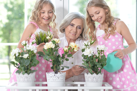 granny with granddaughters watering flowers Stock Photo