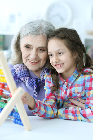Grandmother teaching her granddaughter to use abacus
