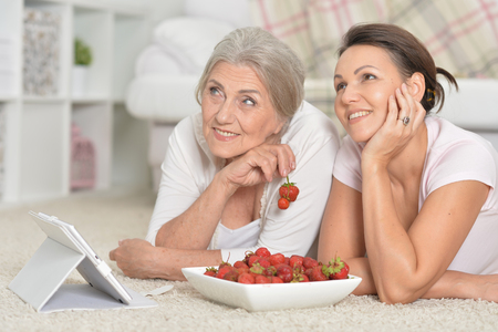 Mother and her adult daughter eating fresh strawberries
