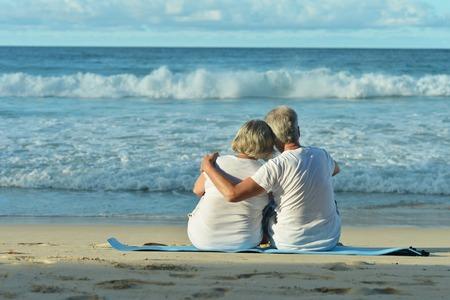 Happy elderly couple resting on sandy beach near tropical resort Stock Photo