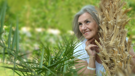 beautiful senior woman behind palm tree Stock Photo
