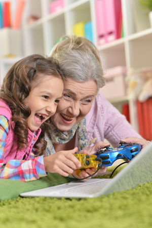 granny with her granddaughter playing computer gam Stock Photo