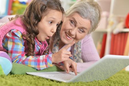 grandmother and daughter using laptop