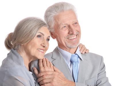 hugging senior couple on white background