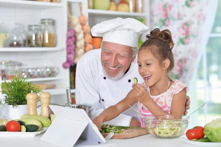 man preparing dinner with granddaughter