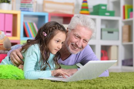 senior man with his granddaughter using laptop 写真素材