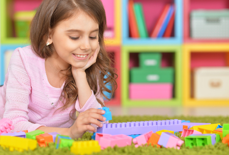Cute girl playing with plastic blocks Stock Photo
