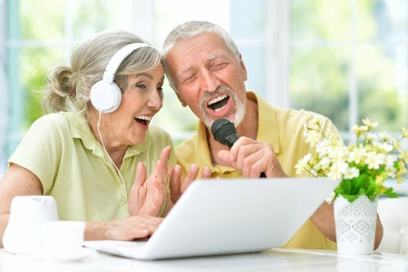 happy senior couple singing karaoke with laptop