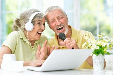 Feliz pareja senior cantando karaoke con laptop